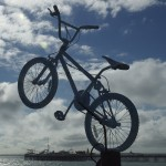 A blue painted BMX leaps from the top of a disused telegraph pole, against a blue sky with puffy white clouds, and with Brighton Pier in the background