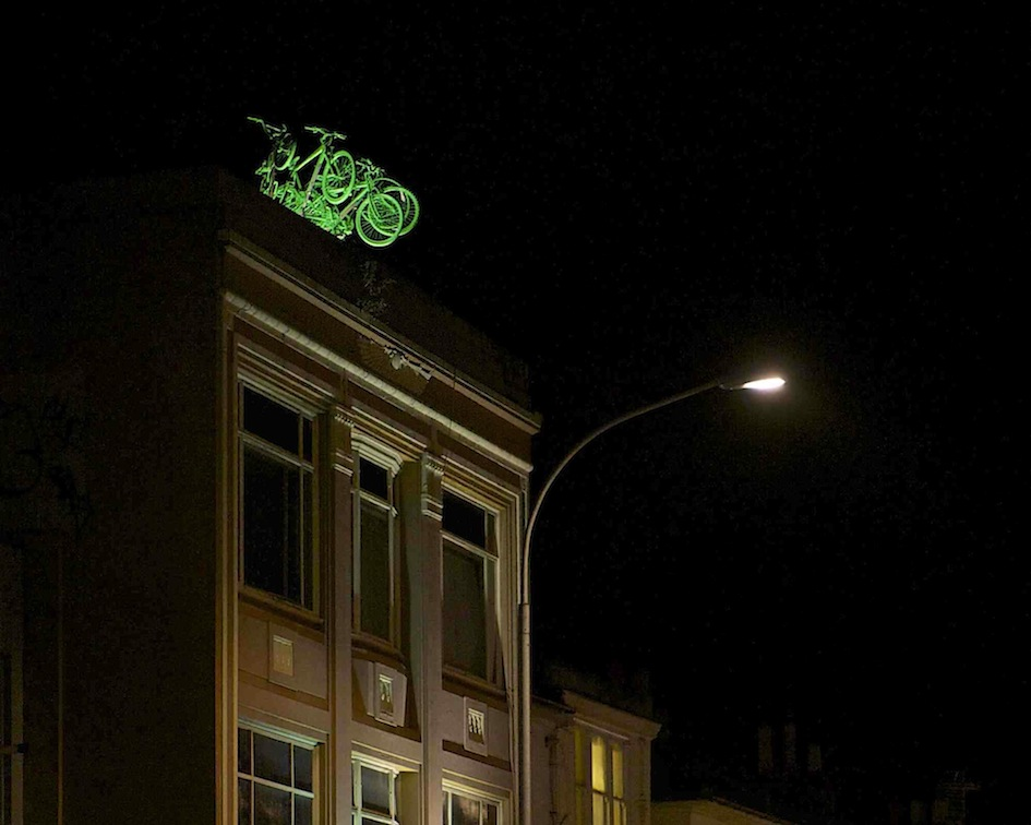 Five green painted bikes sit on the roof of an art deco building, glowing bright green under the lights