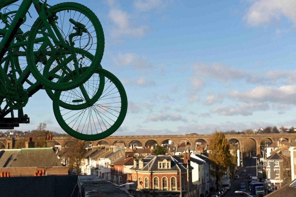 Green bike wheels against a blue sky, tower over the Brighton skyline