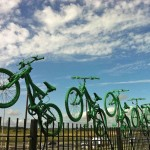 Seven green bikes atop Cyclopark's fence, overlooking the A2