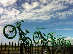 Five green painted bicycles leap from the top of a fence into a blue sky dotted with clouds
