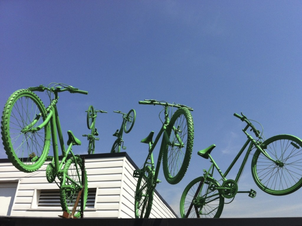 Five green bikes leap from two levels of the rooftop of Putney Leisure Centre