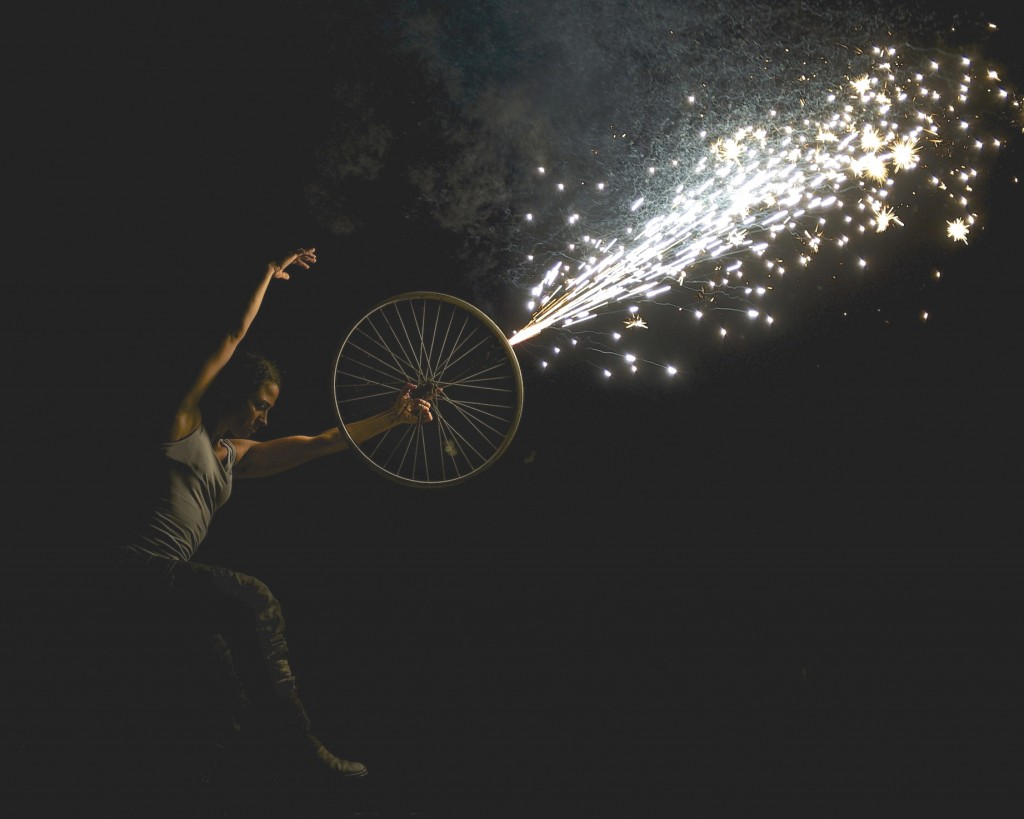woman dances with a bike wheel from which shoots a sparkling firework (don't try this at home!)